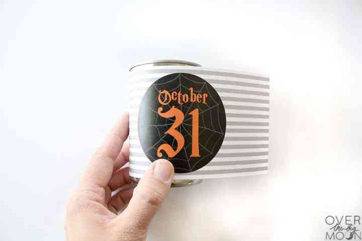 A Halloween Tin Can Wrapper being wrapped around a tin can.