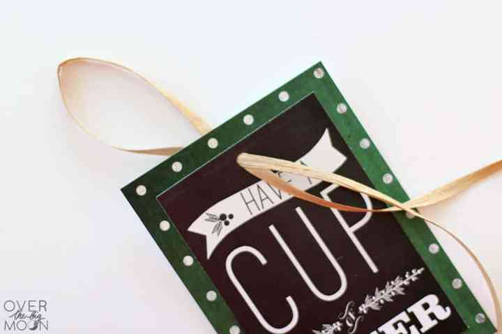 A printable chalkboard DIY Christmas ornament with raffia threaded through a hole punch at the top of it.