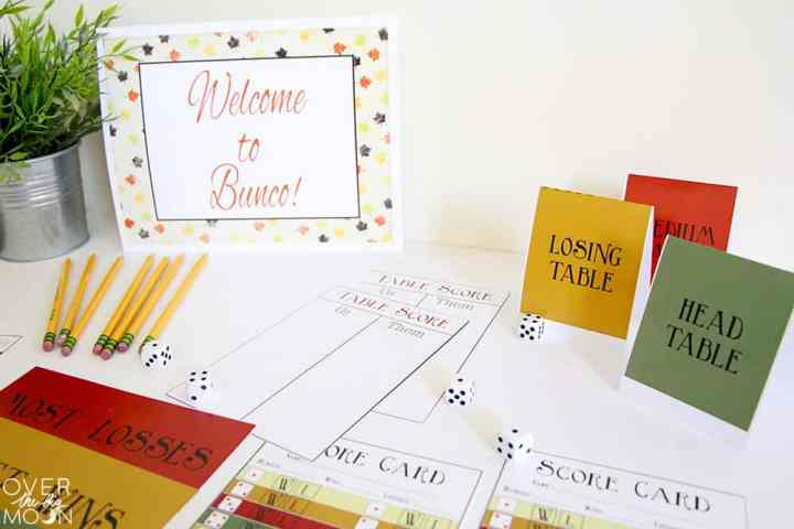 An entire bunco printable pack displayed on a table. The score cards, prize tags, cheat sheet, table cards and welcome sign.