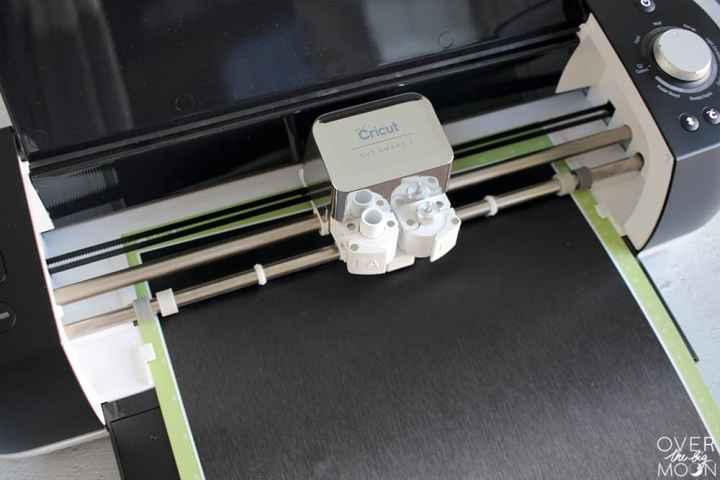 A close up shot of a black Explore Air 2 machine cutting black vinyl.