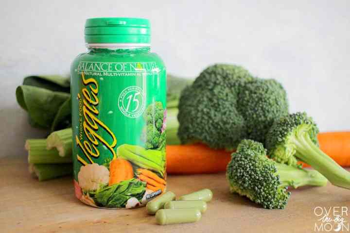 A green bottle of Balance of Nature Veggie Capsules standing a wood cutting board, with a pile of vegetables behind the bottle. In front of the bottle is a small pile of green veggie capsules.