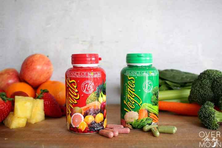 Two pill bottles on a brown cutting board with fruits and vegetables in the background. One bottle is green and labeled Veggies and one is red and labeled fruits. In front of each bottle is a few of the capsules from the bottles.