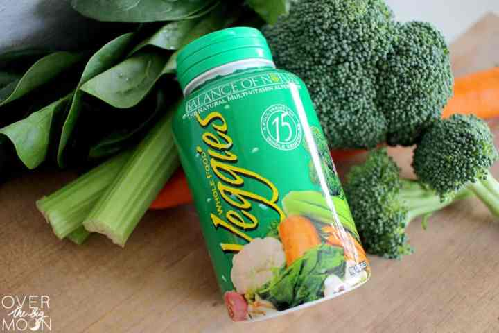 A green bottle of Balance of Nature Veggie Capsules leaning up against a pile of vegetables, such as spinach, celery, broccoli and carrots.