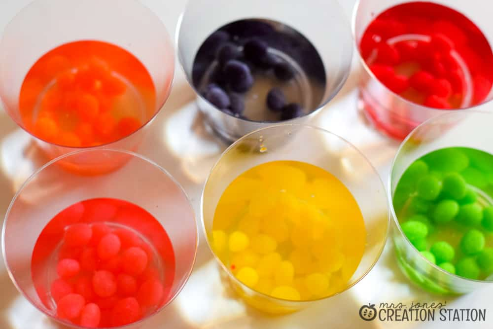 Jelly beans of all colors in cups of liquid, divided by color.