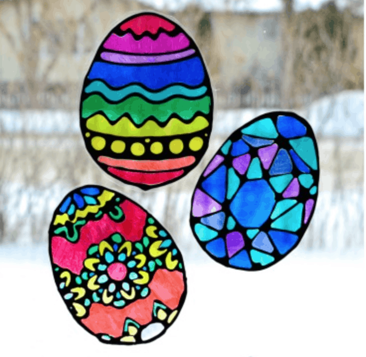 Easter Eggs colored and decorated and hung on windows to let the light shine through the colorful pictures.