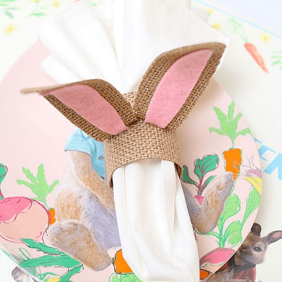 A plate with napkin on it. The napkin has a cute burlap napkin ring on it that looks like a bunny. I