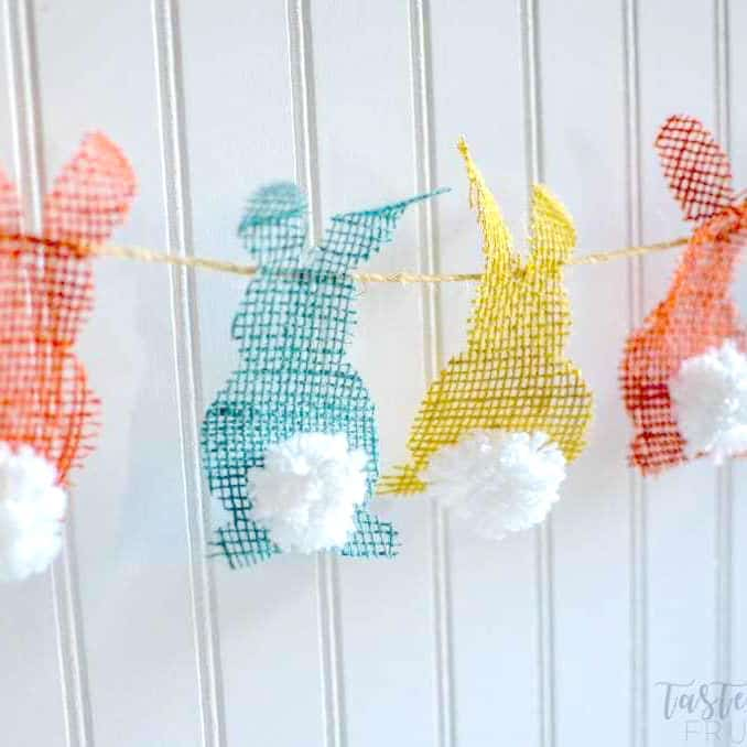 A bunny bunting cutout of orange, blue and yellow burlap with pom pom tails on them. They're attached to a piece of twin and hanging against a white slat wall.