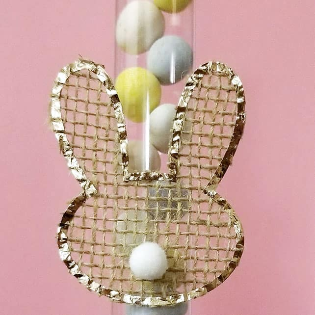 A bunny head shape cut from burlap attached to a treat tube to create a Easter gift.