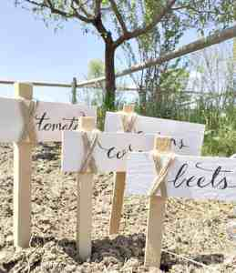 4 Garden Markers made from wood and twine that have the words beets, carrots, tomatoes and onions on them. A tree is in the background.