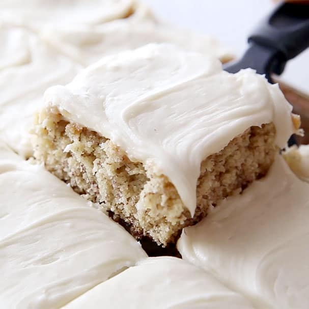 Cream Cheese frosted Banana Bars cut into squares and a black spatula serving a square.