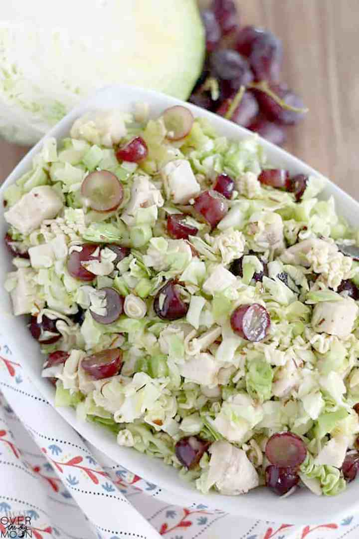 A white bowl of a cabbage salad with chicken, ramen pieces, grapes and green onions. In the background is a ½ head of cabbage and sliced purple grapes.