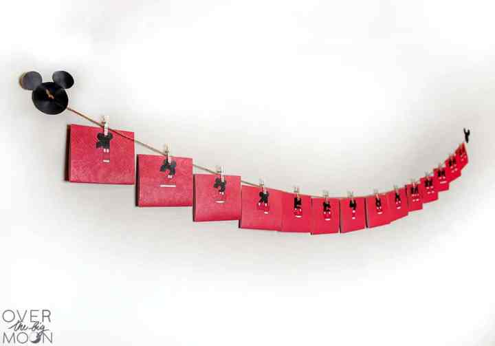 A printable Disney Countdown hanging on a white wall. The countdown is made of Red Printable Cards hanging on a twine. At the each end of the twine is a black Mickey Head.