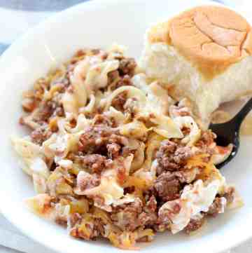 A casserole of egg noodles, hamburger and sauce served on a white plate with a roll next to it.