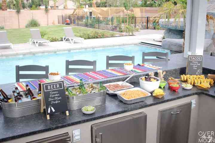 An outdoor kitchen with beer, tacos, beans, rice and more. In the background there's a pool and grass area.