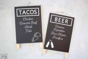 Two signs made with vinyl -- one says Tacos and lists 4 different kinds of tacos and the 2nd sign says Beer and lists 4 different kinds of beer.