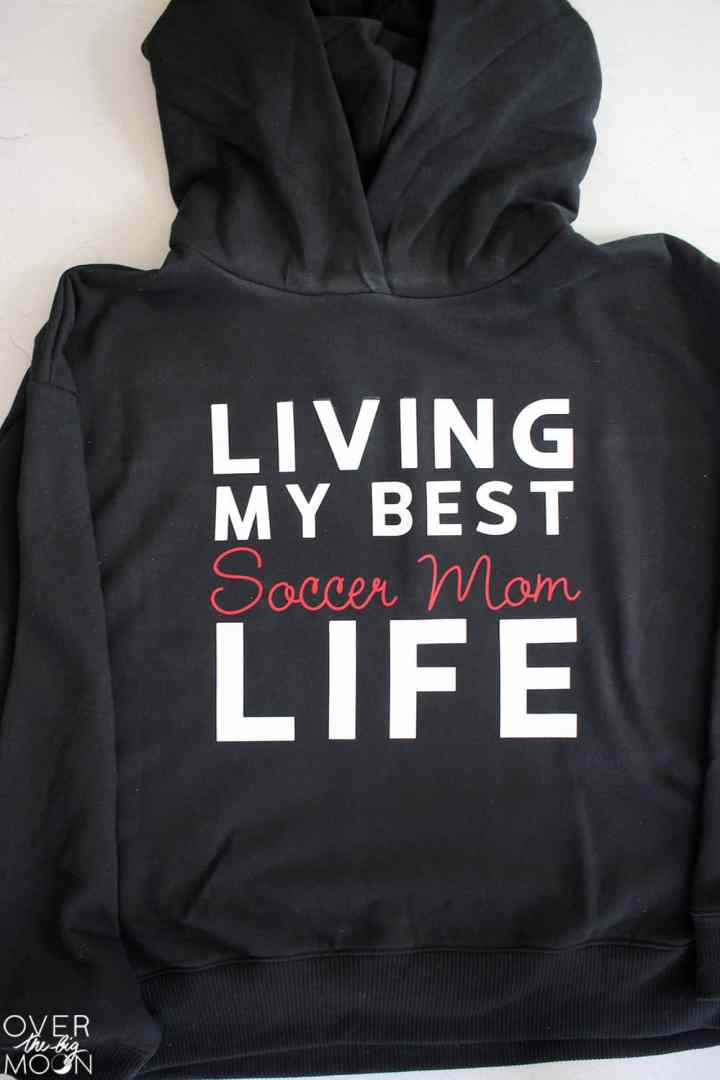 A black hoodie with the saying Living My Best Soccer Mom Life on it.