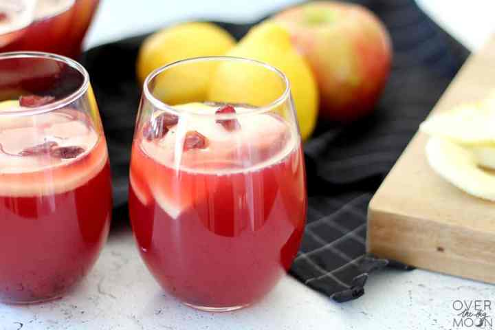 Two small cups filled with a red punch and garnished with apple slices and craisins. Behind it is a black napking with an apple and lemons.