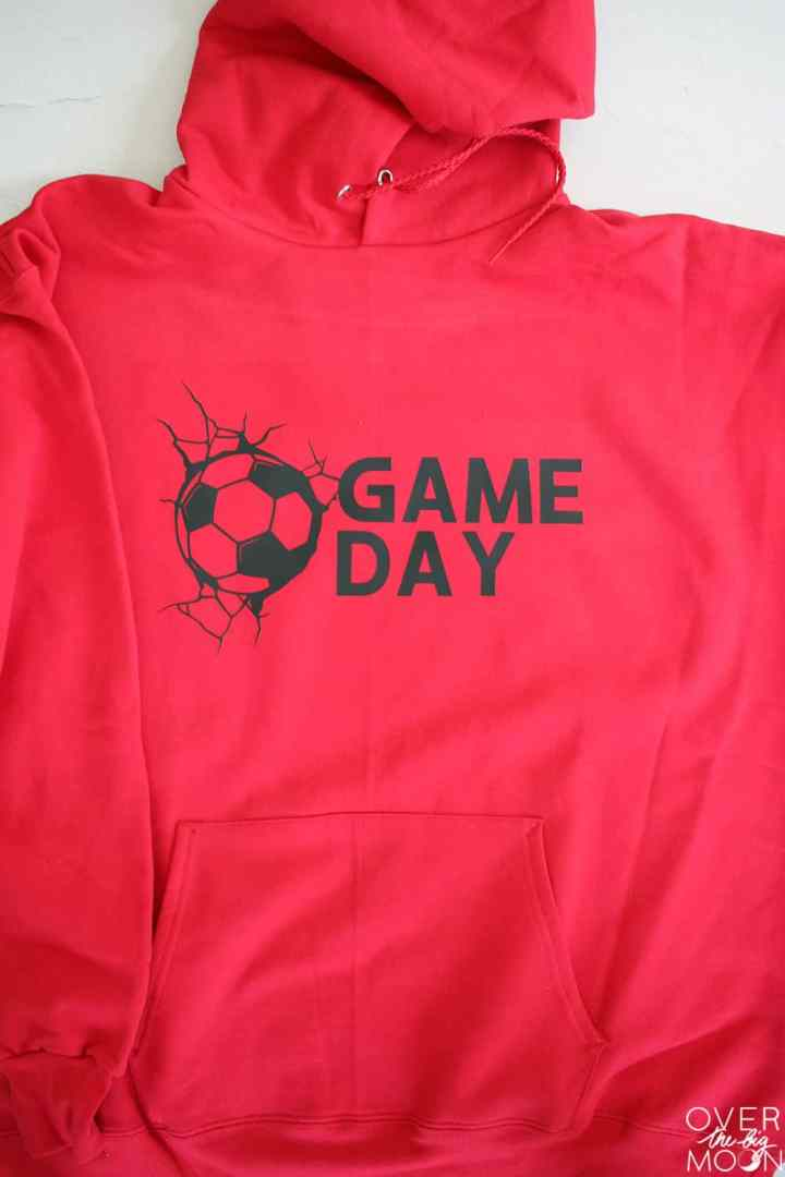 A red hoodie that says Game Day on it with a soccer ball to the left of the words.