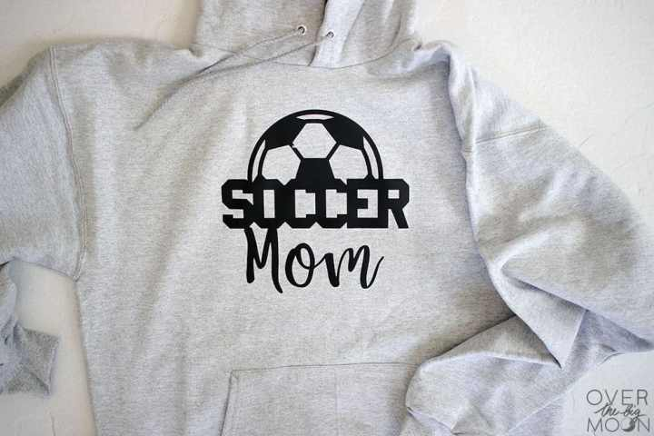 A gray hoodie that says Soccer Mom on it with a half of a soccer ball coming out the top of the word Soccer.