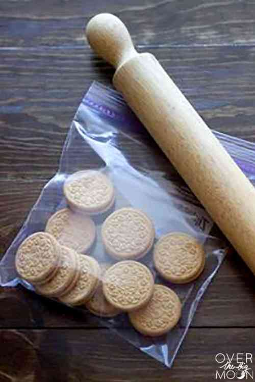 A ziplock bag of golden oreos with a rolling pin next to it.