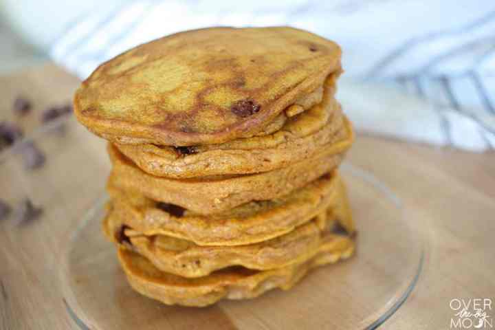 A stack of pumpkin chocolate chip pancakes on a clear plate.