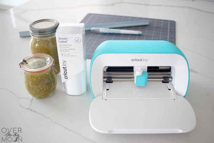 Cricut Joy machine sitting on a white counter, with a package of Smart Label, 2 jars of Cilantro Lime Enchilada Sauce, a cutting mat, ruler and craft knife.