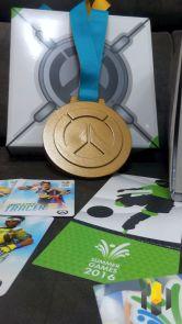 Detalhe da medalha, ingresso e cards.