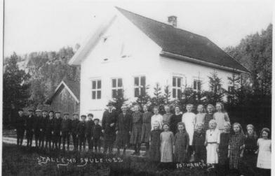 """Bildet viser elevene utenfor skolehuset på Stallemo i 1922.Mellom """"guttesiden"""" og """"jentesiden"""" de to lærerne Thorvald Haugenes og Gunhild Loland."""