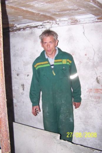 Kenneth Kleveland hjelper med å fjerne deler av den gamle fjøsinnredningen, en vanskelig og arbeidskrevende jobb.