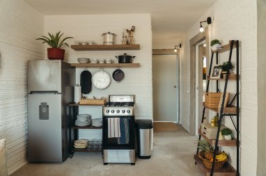 a-modest-kitchen-offers-the-essentials-an-oven-with-a-range-a-refrigerator-and-shelving