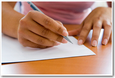 Person writing on a paper with a pen
