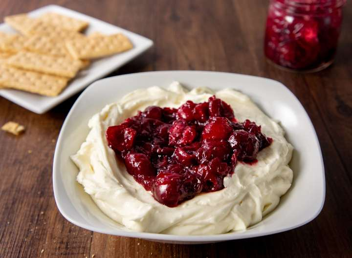 Cheesecake dip in a bowl topped with cherry pie filling