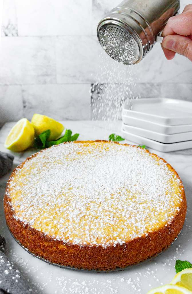 Lemon Ricotta cake being dusted with powdered sugar