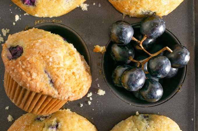 Grape muffins in a muffin pan with grapes
