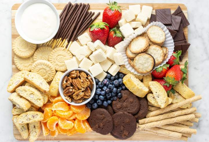 Dessert charcuterie board with an arrangement of cookies, fruit and desserts.