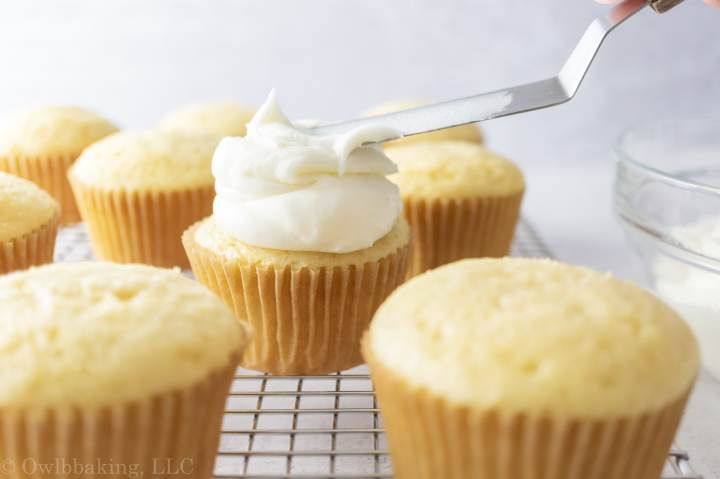 Adding a dollop of sour cream frosting on a cupcake