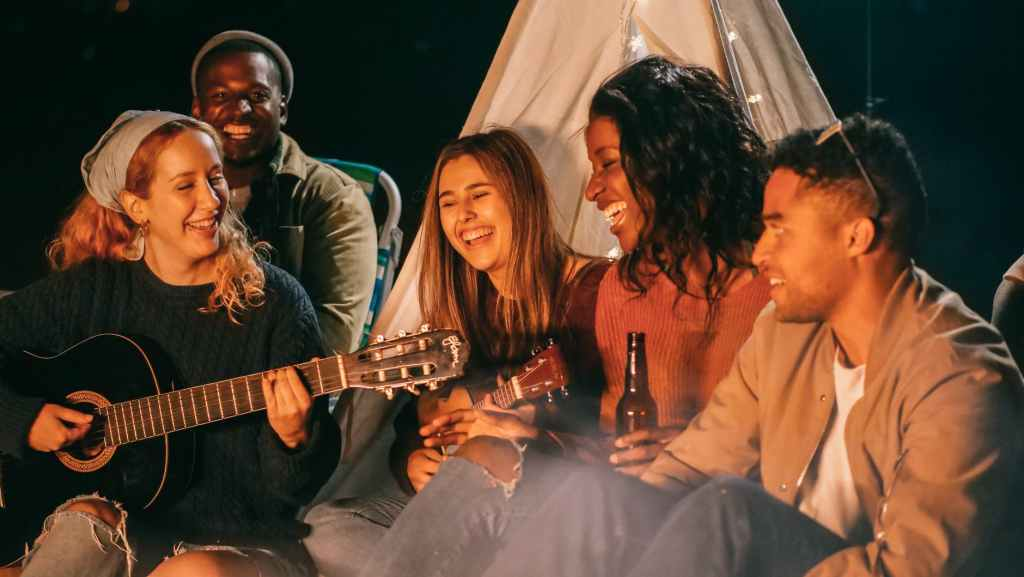 group of friends singing while sitting on beach sand