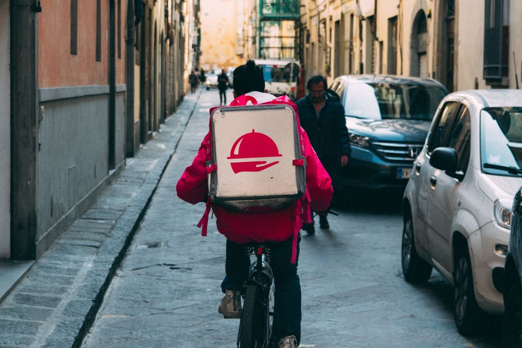 Man on a bicycle wearing a delivery bag on his shoulders with the logo of Foodora, a food delivery service.