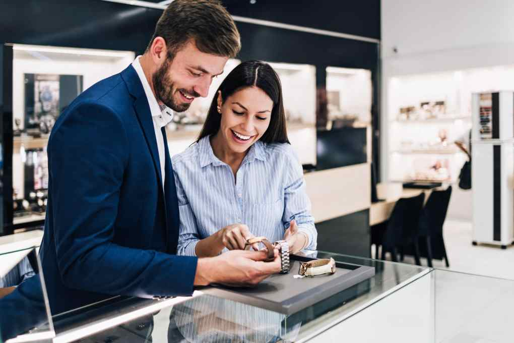A young couple shopping for watches at a jewelry store.