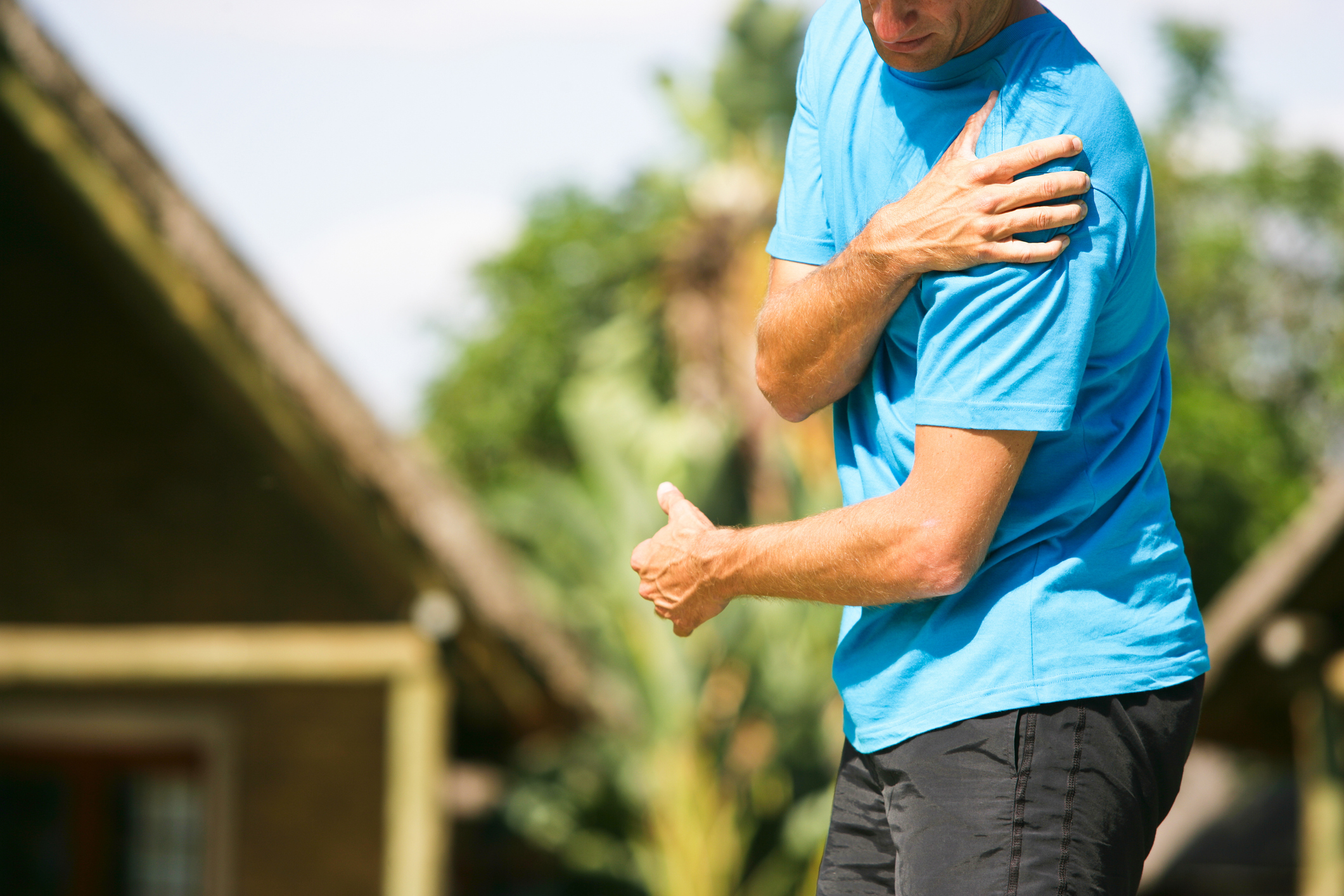 man with an injured rotator cuff clutching his shoulder