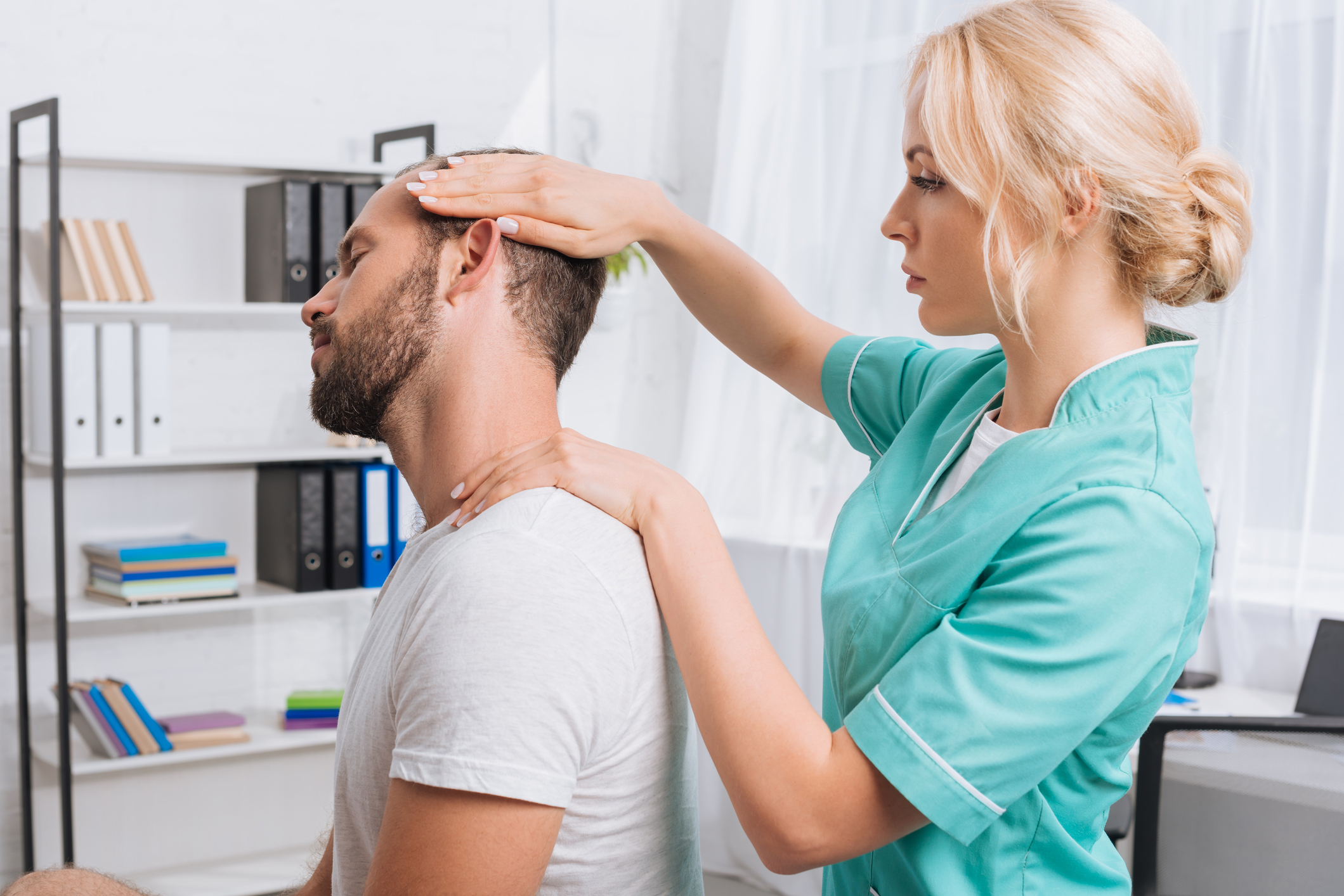 Benefits of chiropractic care for anxiety. Female chiropractor working on a male patient's neck.