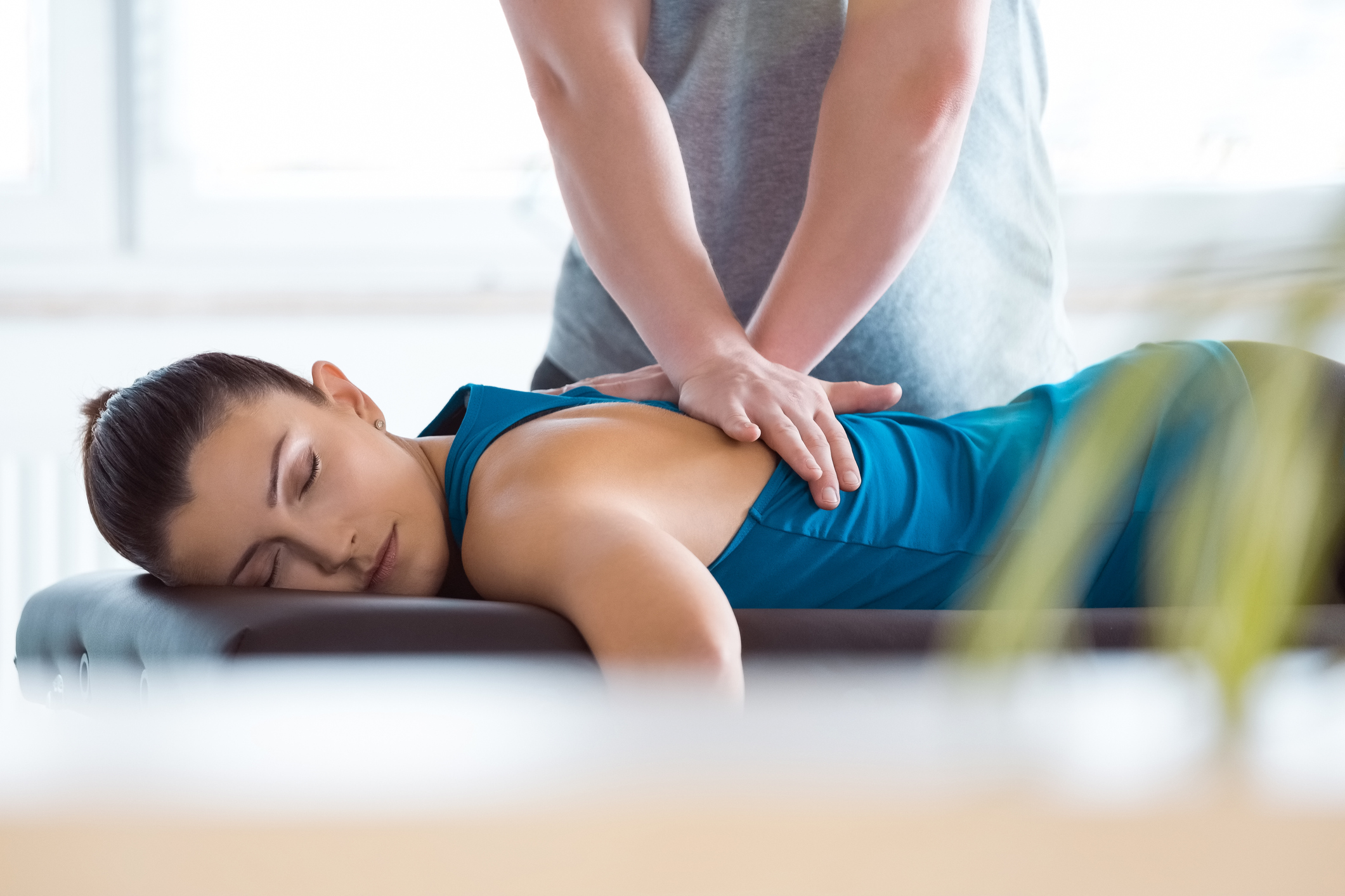 Woman lying on a chiropractor's table having her back manually adjusted