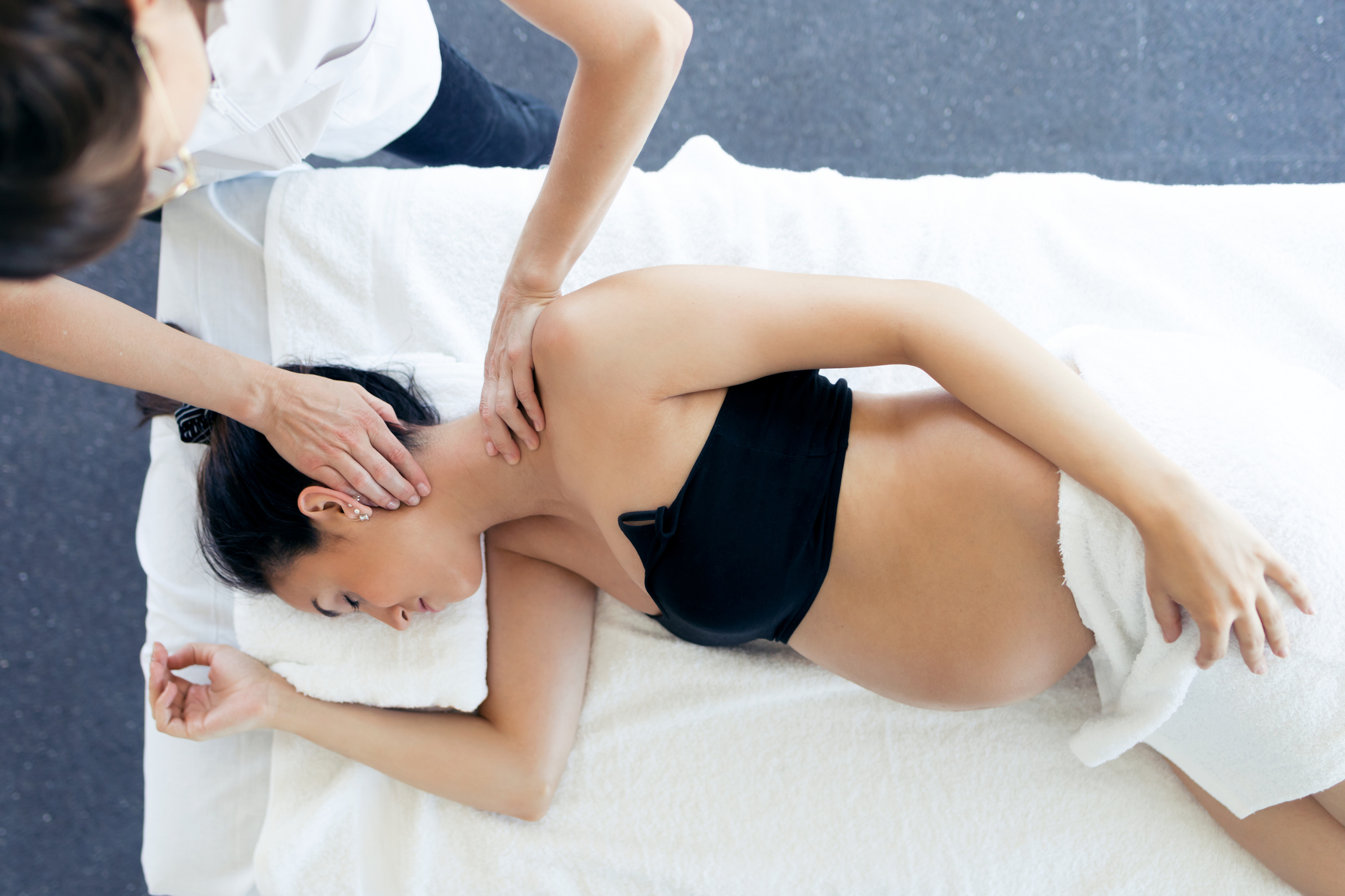 Shot of pregnant woman receiving chiropractic treatment on her neck in a clinic.