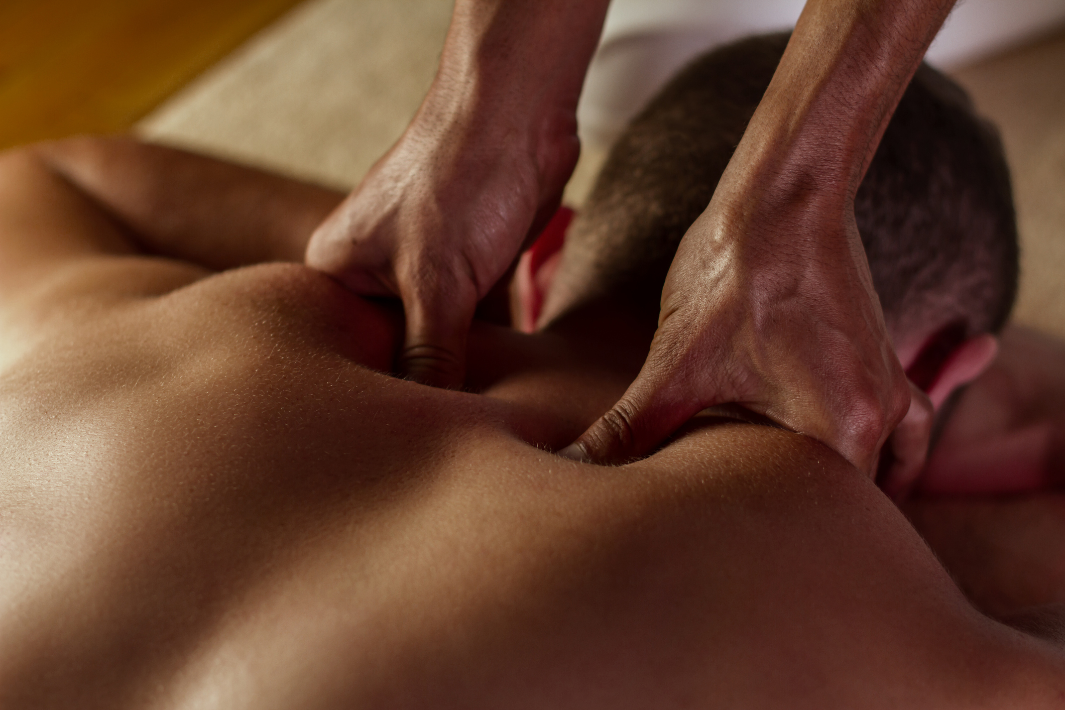 A man receiving deep tissue massage on his shoulders and neck.