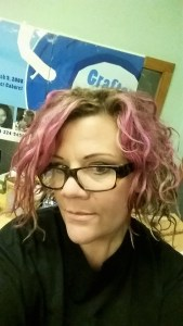 Angie Mack Reilly with pink hair and Grafton City Blues poster