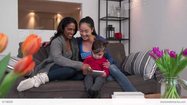Lesbian Couple Using Ipad Tablet With Child Happy Stock Video Footage