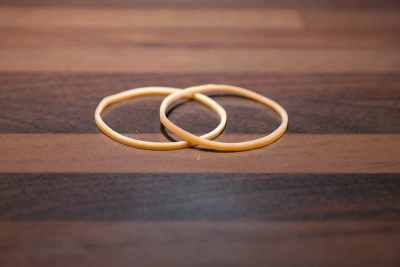 Two brown rubber bands on wooden surface