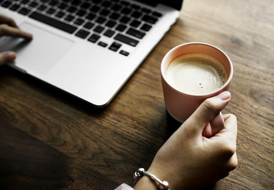 person holding mug using macbook