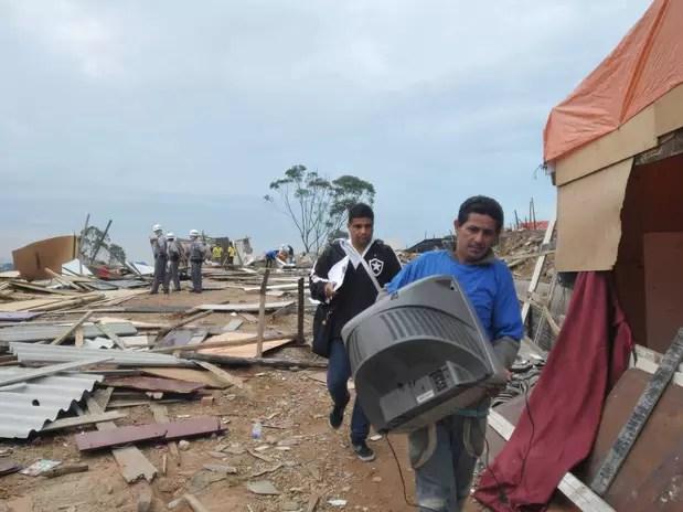 Homem retira pertences do terreno que havia sido ocupado ilegalmente na zona sul de São Paulo Foto: Adriano Lima / Brazil Photo Press