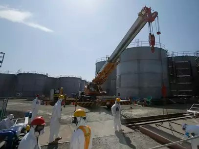 Trabajadores de la operadora Tokyo Electric Power Co. trabajan cerca de tanques de agua radiactiva en la planta nuclear de Fukushima Dai-ichi, en Japón Foto: AP